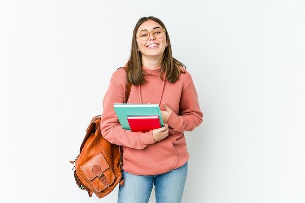 Jonge student vrouw geïsoleerd op witte bakcground lacht vrolijk en heeft plezier met handen op de buik