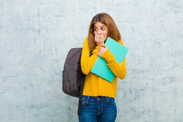 Jonge student vrouw op zoek bezorgd, angstig, gestrest en bang, nagels bijten en op zoek naar laterale kopie ruimte tegen grunge muur muur