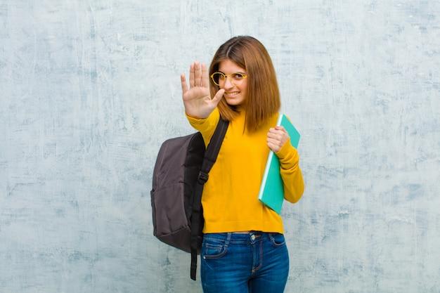 Jonge student vrouw op zoek serieus, ongelukkig, boos en ontevreden verbieden toegang of zeggen stop met beide open palmen op grunge muur