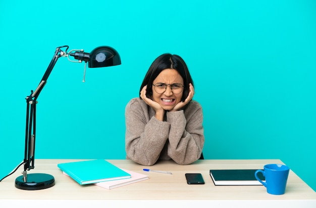 Jonge student vrouw van gemengd ras die gefrustreerd een tafel bestudeert en oren bedekt