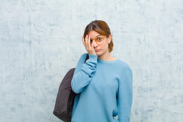 Jonge student vrouw verveeld, gefrustreerd en slaperig na een vermoeiende, saaie en vervelende taak, gezicht met hand grunge muur houden