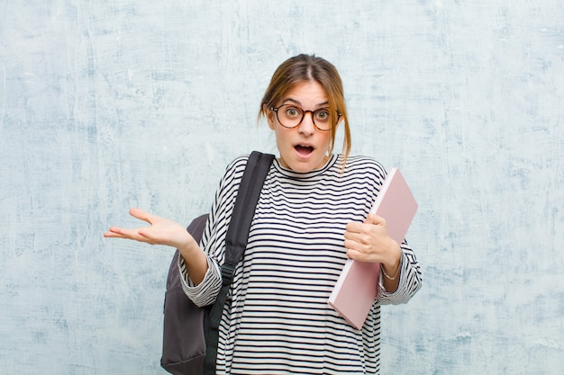 Jonge student vrouw voelt zich extreem geschokt en verrast, angstig en in paniek, met een gestresste en gruwelijke blik tegen grunge muur