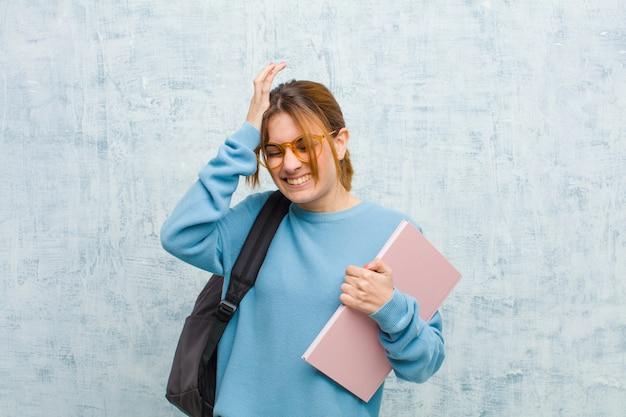Jonge student vrouw voelt zich gestrest en angstig, depressief en gefrustreerd met hoofdpijn, beide handen opheffen