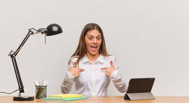 Jonge student vrouw werkt op haar bureau verrast, voelt zich succesvol en welvarend