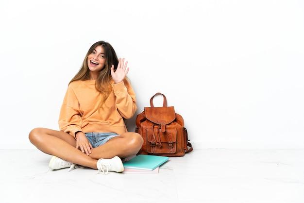 Jonge student vrouw zittend op de vloer met een laptop geïsoleerd op een witte achtergrond saluerend met de hand met gelukkige expressie