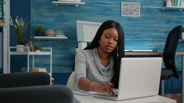 Jonge student werkt op afstand van huis bij marketingstrategie die financiële grafieken op notebook schrijft