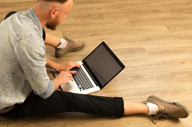Jonge student werkt thuis op zijn laptop