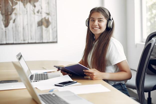 Jonge student zit aan de tafel en gebruik de laptop