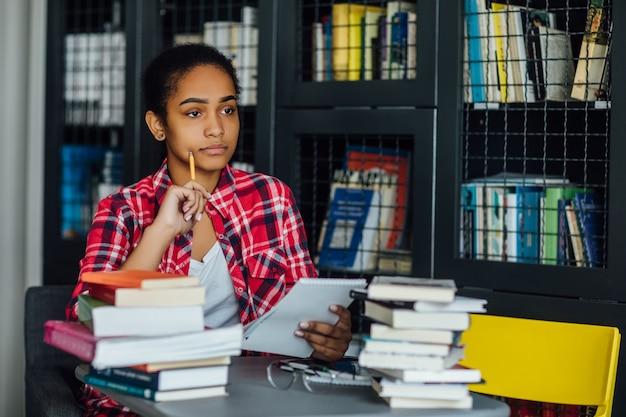 Jonge student zit aan universiteitsbibliotheek tijdens pauze van studeren