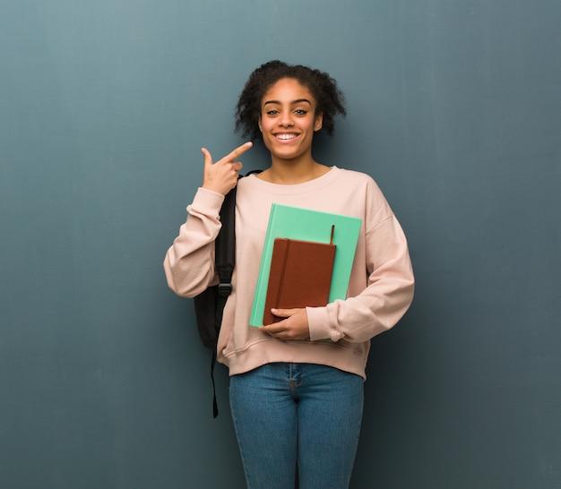 Jonge student zwarte vrouw glimlacht, wijzend op mond. ze houdt boeken vast.