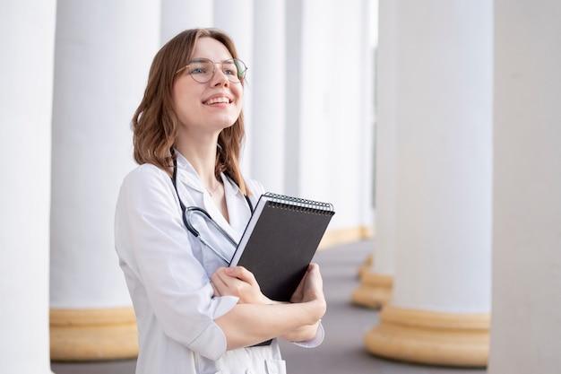 Jonge studente aan een medische universiteit die zich in de gang bevindt, portret van een aantrekkelijke verpleegster dichtbij het ziekenhuis, gelukkige vrouwelijke arts met een stethoscoop in uniform