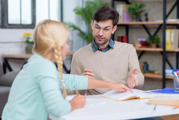 Jonge studente die aan de leraar verklaart
