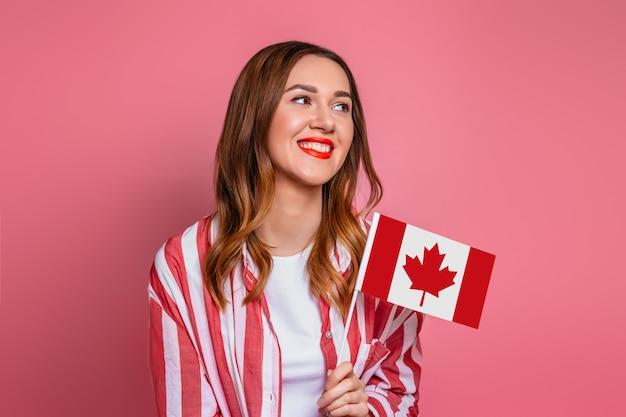 Jonge studente die gestreept overhemd dragen die en een kleine vlag van canada glimlachen houden die over roze ruimte, de dag van canada wordt geïsoleerd