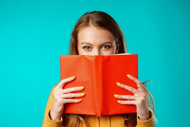 Jonge studente die haar gezicht achter het boek verbergt