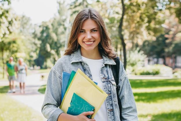 Jonge studente die in het park glimlacht. de leuke studente houdt omslagen en notitieboekjes in handen. leren, onderwijs concept