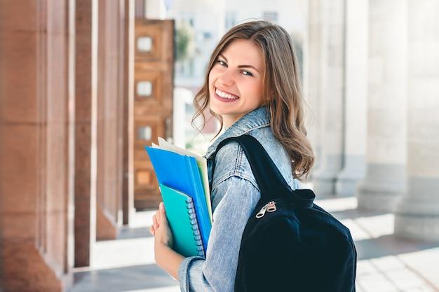 Jonge studente die tegen universiteit glimlacht. de leuke studente houdt omslagen en notitieboekjes in handen. leren, onderwijs