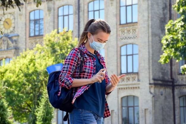 Jonge studente in beschermend masker en schooltas op haar schouder staat buiten in de buurt van de universiteit en reinigt handen met antisepticum. terug naar school na de covid-19-pandemie. nieuw normaal.