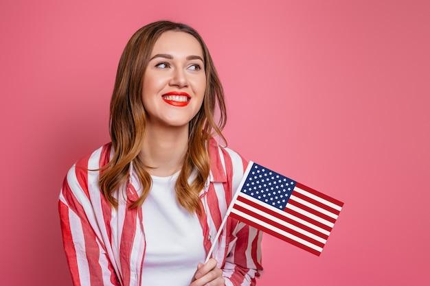Jonge studente met rode lippenstift op lippen houdt amerikaanse kleine amerikaanse vlag en glimlacht geïsoleerd over roze ruimte 4 juli onafhankelijkheidsdag van amerika