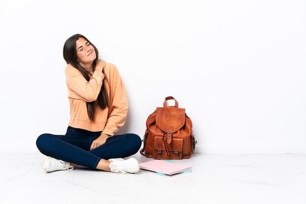 Jonge studenten braziliaanse vrouw zittend op de vloer die lijdt aan pijn in de schouder omdat ze zich heeft ingespannen