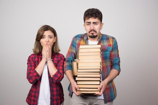 Jonge studenten die verdrietig kijken en boeken vasthouden op een grijze achtergrond.
