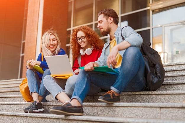 Jonge studenten glimlachen en huiswerkproject doen
