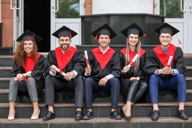 Jonge studenten in bachelor gewaden en met diploma's zittend op trappen buiten