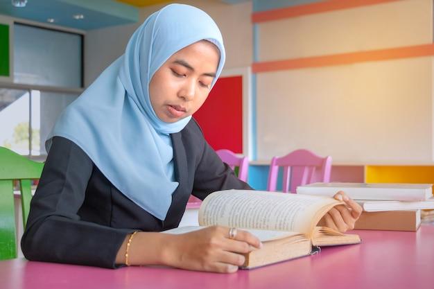 Jonge studenten islamitische vrouw. ze zit en leest een boek.