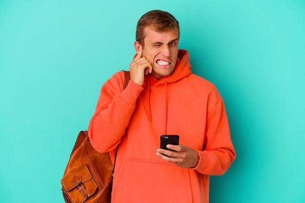 Jonge studenten kaukasische man die een mobiele telefoon houdt die op blauw wordt geïsoleerd dat oren behandelt met handen.