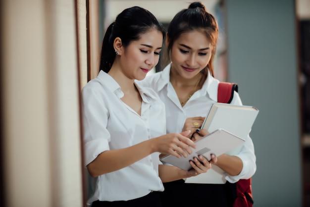 Jonge studenten leren, bibliotheekboekenkasten