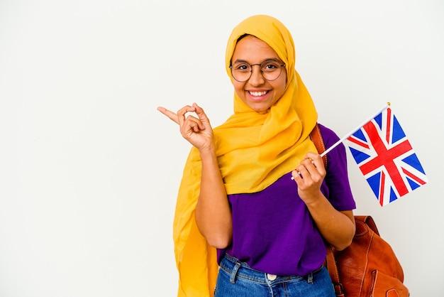 Jonge studenten moslimvrouw die op witte achtergrond wordt geïsoleerd die en opzij glimlacht richt, die iets op lege ruimte toont.
