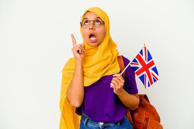 Jonge studenten moslimvrouw die op witte achtergrond wordt geïsoleerd die ondersteboven met geopende mond richt.