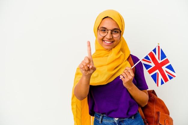 Jonge studenten moslimvrouw op wit die nummer één met vinger toont.