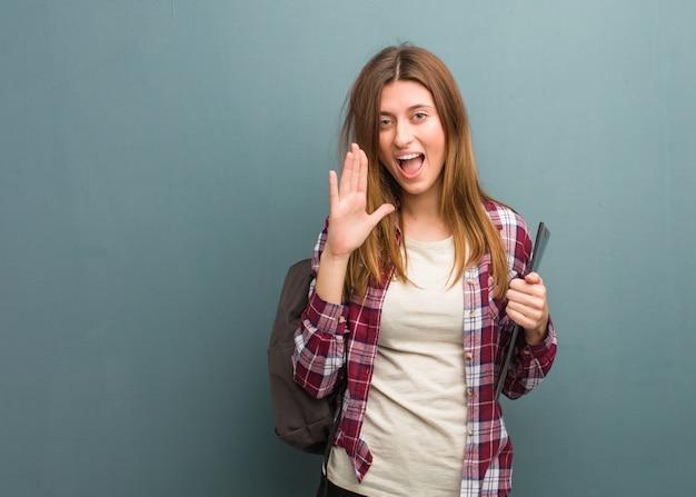 Jonge studenten russische vrouw die iets gelukkig aan de voorzijde schreeuwen