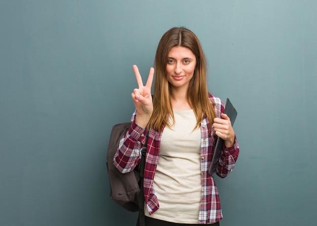 Jonge studenten russische vrouw die nummer twee toont