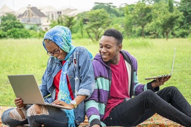 Jonge studenten zitten in een park en werken samen op hun laptop aan een universiteitstaak