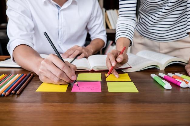 Jonge studentencampus of klasgenoten helpen een vriend bij het inhalen van het werkboek en het leren van bijlessen in de klaspraktijk die examen voorbereidt