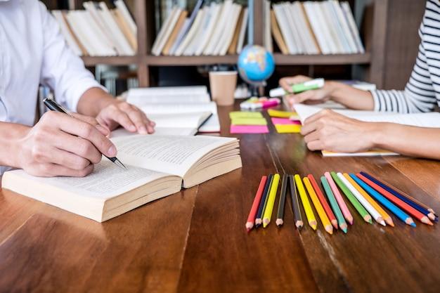 Jonge studentencampus of klasgenoten helpt een vriend bij het inhalen van een werkboek en het leren van bijlessen in de klas