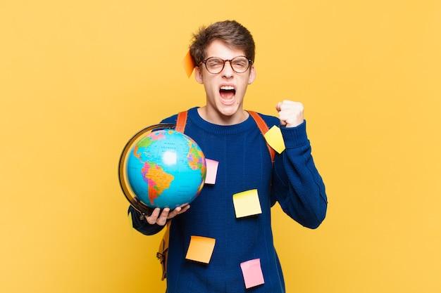 Jonge studentenjongen die agressief schreeuwt met een boze uitdrukking of met gebalde vuisten om succes te vieren