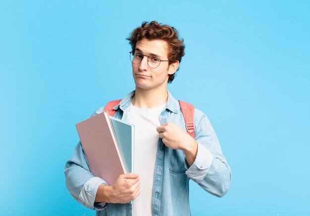 Jonge studentenjongen die er arrogant, succesvol, positief en trots uitziet, wijzend naar zichzelf