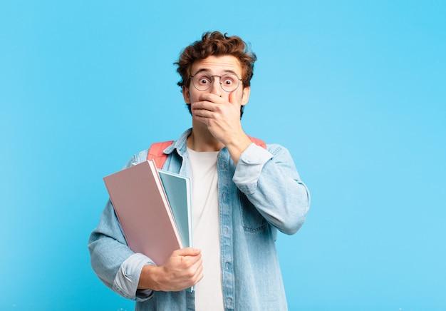 Jonge studentenjongen die mond bedekt met handen met een geschokte verbaasde uitdrukking die een geheim houdt of oeps zegt saying