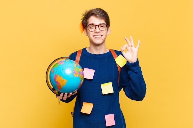 Jonge studentenjongen die zich gelukkig, ontspannen en tevreden voelt, goedkeuring toont met een goed gebaar, glimlachend