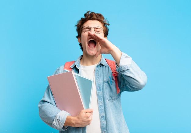 Jonge studentenjongen die zich gelukkig, opgewonden en positief voelt, een grote schreeuw geeft met de handen naast de mond, roept,