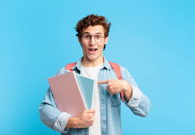 Jonge studentenjongen die zich gelukkig, verrast en trots voelt, wijzend naar zichzelf met een opgewonden, verbaasde blik