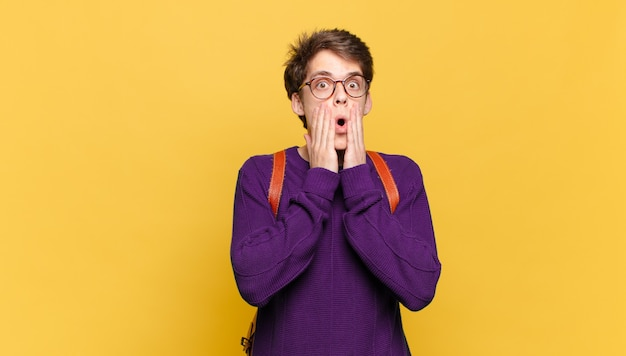 Jonge studentenjongen die zich geschokt en bang voelt en er doodsbang uitziet met open mond en handen op de wangen