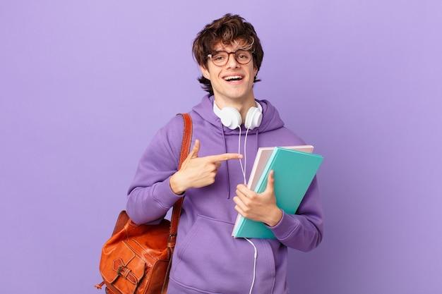 Jonge studentenman die vrolijk lacht, zich gelukkig voelt en naar de zijkant wijst