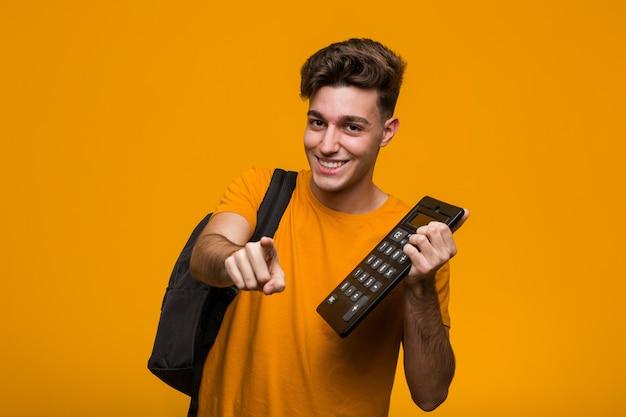 Jonge studentenmens die een calculator en het richten houdt