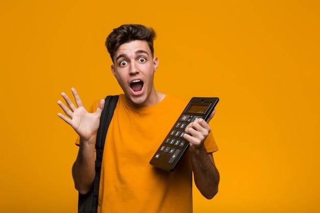 Jonge studentenmens die een calculator gelukkig, glimlachend en vrolijk houdt.