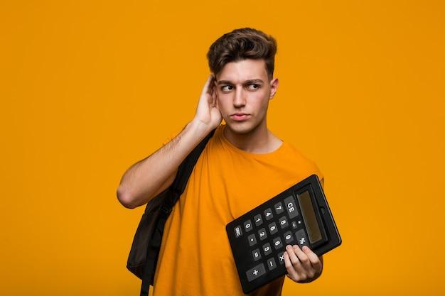 Jonge studentenmens die een calculator houdt die zelfverzekerd met gekruiste armen glimlacht.