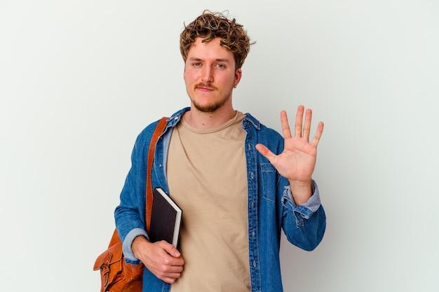 Jonge studentenmens die op wit wordt geïsoleerd lacht vrolijk tonend nummer vijf met vingers.