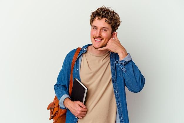 Jonge studentenmens die op witte muur wordt geïsoleerd die een mobiel telefoongesprekgebaar met vingers toont.